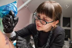 Young Cute Girl Tattoo Master At Work On Patterning On The Models
