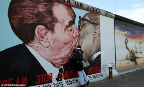 a woman kisses russian artist dimitry vrubel s famous mural of brezhnev kissing honecke on famous berlin wall artists with world leaders gather for 7m berlin wall 20th anniversary