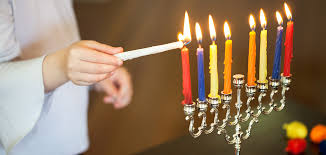 girl lighting the menorah for hanukkah