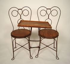 an unusual antique ice cream parlor double seater with attached table the chairs made from