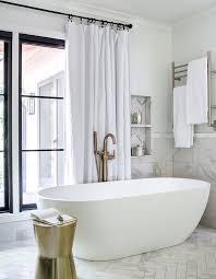 marble herringbone tiled niche over freestanding bathtub