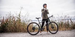 a cyclist adjusting her helmet before getting on her bike
