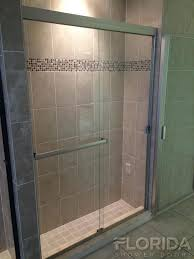 frameless sliding shower door brushed nickel with a pound on handle and towel bar