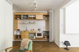 this tiny kitchen features both open and closed shelving on the top and bottom parts of the kitchen creating the ability to display the beautiful and hide