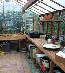 home greenhouse designs with wooden frames and glass material with long wooden shelf under rectangle