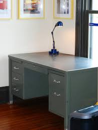 shown here is a steelcase 60 stick leg tanker desk with light blue frame with white drawers and a white formica top