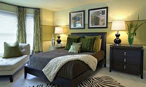 Green and black bedroom with striped accent wall.