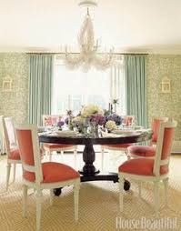 the white chairs and c chandelier make a big gany table feel lighter than it