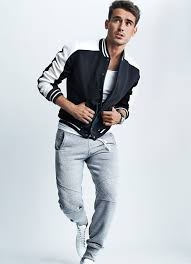 a baseball jacket and grey running pants are a perfect pairing to be utilised at the