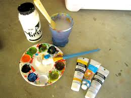 assorted acrylic paints and paint brushes