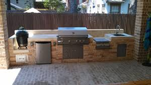 this outdoor kitchen by outdoor homescapes of houston features from left a big green