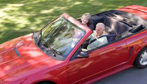 couple in convertible car smiling auto insurance