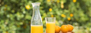 orange juice in glass and pitcher