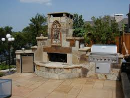 outside kitchen with grills and vintage stone fireplace openair