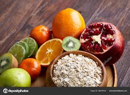 bowl with oatmeal flakes served with kiwi lime lemon orange tangerin apple and pomergranate on wooden tray over rustic wooden background flat lay