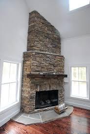 stone corner fireplace design with wood mantel beam