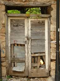 very old wooden doors with large holes in bottom portion