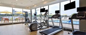 fitness center with cardio machines facing windows and tvs