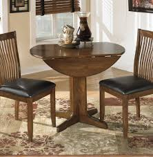 small round drop leaf dining table with wooden base painted with dark brown color and 2
