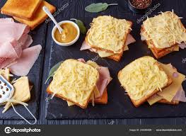 french toast croque monsieur prepared to bake toasted er bread with slices of boiled ham and emmental cheese on a stone tray and ings on a