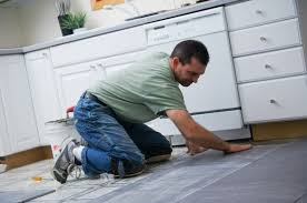 man laying tile in a kitchen