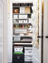 storage closet with various bins boxes and over the door shoe organizer