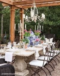 whimsical garden features a french style concrete dining table seating eight wrought iron dining chairs with concrete outdoor