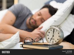 Young Man Sleeping In His Bedroom. Man Sleeping With An Alarm Clock In  Foreground.
