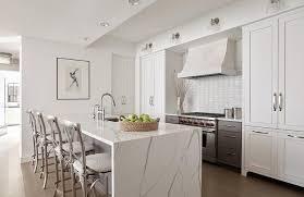 calcutta quartz waterfall countertop island along with silver x back stools incorporate unrefined and organic materials into a contemporary kitchen