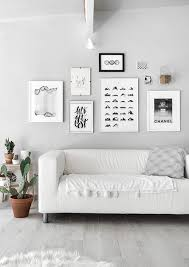 For a modern look, go black and white with your gallery wall. To add a  little color, place a small plant next to your images.