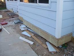 the gaps in the ledger at the far end of the house are where the basement window wells are i am building the deck around them and will install a clear