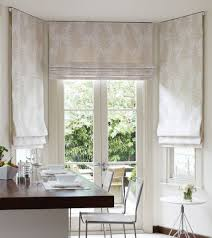 These are mild colored Roman shades which are added to a small breakfast  nook and the