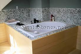 green pebble tile bathtub backsplash