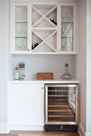 here a wine refrigerator and cabinet create the base of the bar built in shelving and