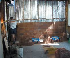 a photo of a worker installing reverse brick veneer on a timber frame