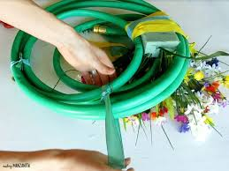 attaching a ribbon hanger to the top of the summer wreath made with a garden hose