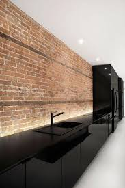 all black kitchen with brick Espace St-Denis by Anne Sophie Goneau