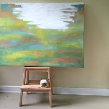 painting over a canvas with white acrylic to repurpose it
