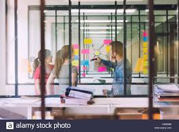 post business office. Groupe Of Casual Business People Working In Front Glass Wall Using Notes Papers Post It. Seen Through Startup Office