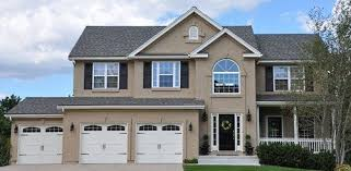 large home painted with 3 colors tan stucco cream trim and black accents including the front door