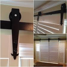 a detail shot of plantation shutters with custom barn door hardware on a sliding gl door