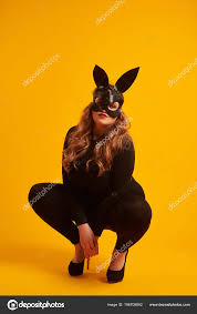 closeup of provocative girl in leather bunny mask sitting on her haunches photo by konstantynov