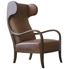 a large elegant and sculptural 1940s wingback chair with sweeping arms and curved headrests