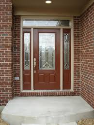 exterior wood entry door with frosted glass insert and red brick wall exterior house design ideas