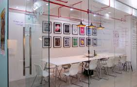 the meeting area in saltycustoms is adorned with bright designs glass walls which doubles as a writing board