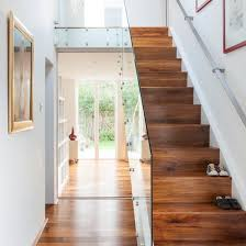 White hallway with walnut and glass staircase