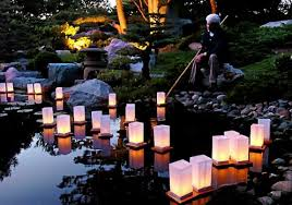 japanese garden lighting. jack sattle uses a bamboo pole to push lanterns back out into the pond in japanese garden lighting