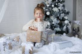 Happy child,5 year old girl in Christmas holidays near a beautiful green tree