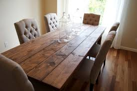 country style long rustic farmhouse dining table made from reclaimed wood with white tufted dining chairs with fabric cover and high back ideas