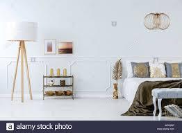 elegant furniture and lighting. Elegant, Golden Decorations In A Luxurious, Light Gray Bedroom Interior With Furniture And Wall Molding Elegant Lighting R